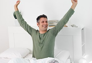 Smiling man stretching in bed