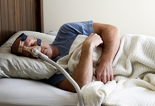 Man sleeping soundly with nasal CPAP and oral appliance
