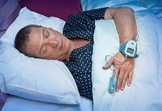A man asleep with a device on his hand to monitor his sleep
