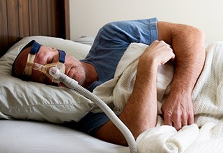 Man sleeping with CPAP system in place