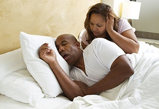 Man asleep snoring loudly woman frustrated awake
