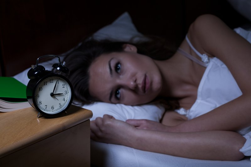 woman lying in bed struggling with stress and sleep