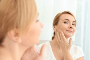 woman applying anti-aging cream in front of a mirror